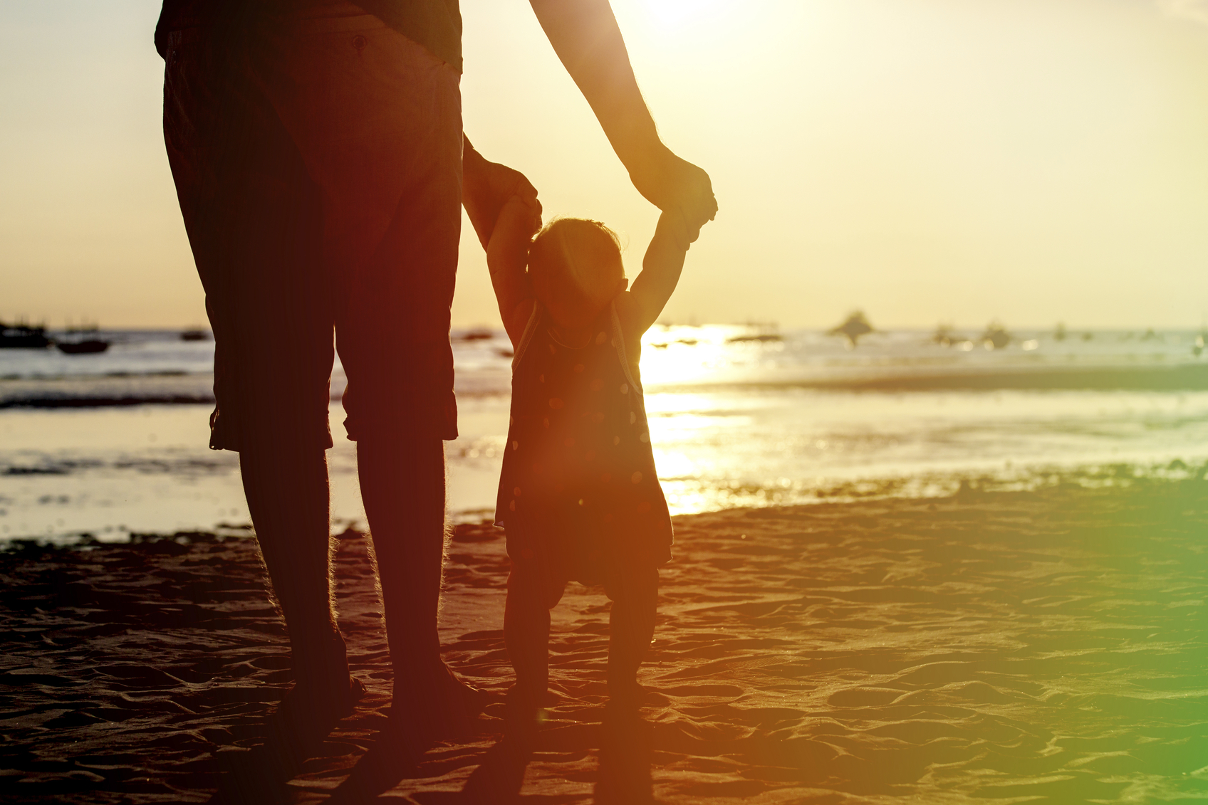 father and little daughter learning to walk on sunset beach